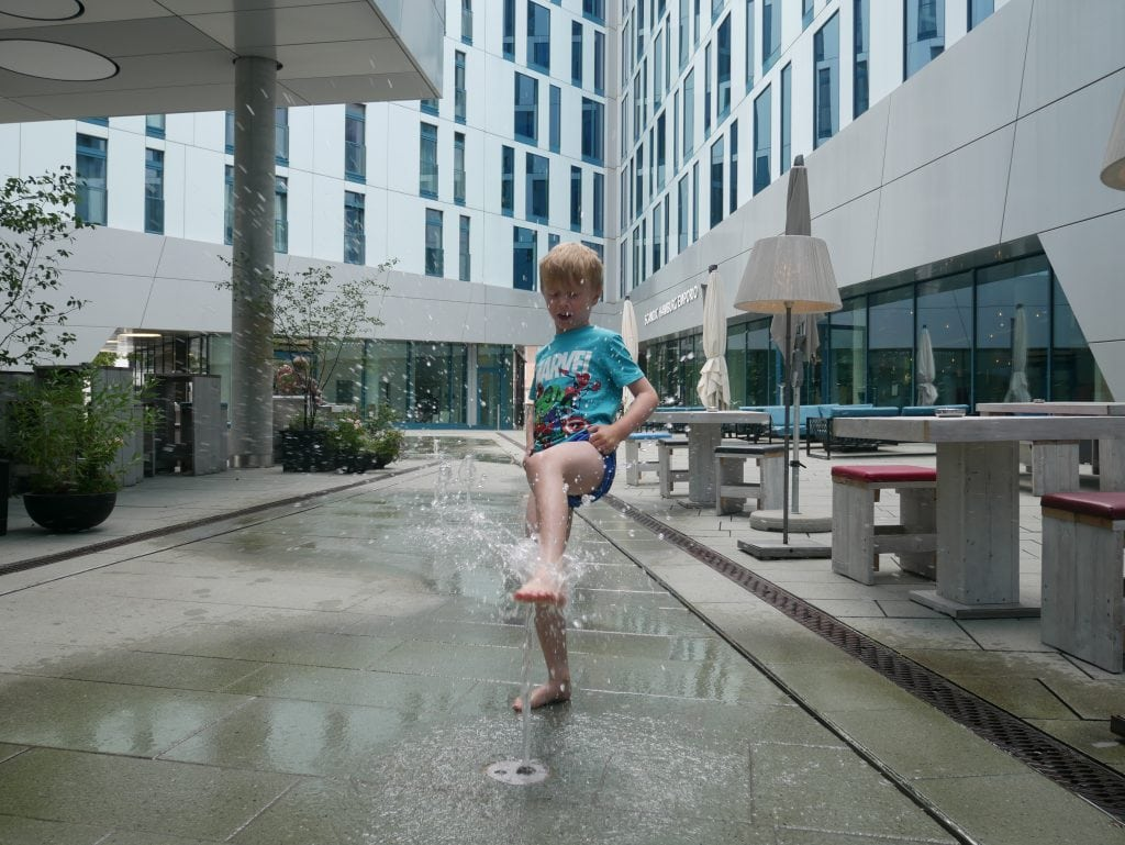 Playing in the water fountains outside and next to the outdoor seating area